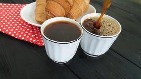 de koffie wordt gegoten in kop van croissant stock video