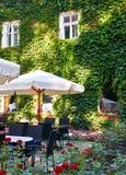 De koffiebinnenland van de de zomerstraat met witte paraplu in groen stadspark, overladen met bloemen en decoratieve elementen Royalty-vrije Stock Fotografie