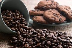 De koffiebonen brokkelden met een kop, op de achtergrond af een plaat van koekjes stock afbeelding
