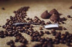 De koffiebonen en het chocoladesuikergoed op jute sluiten omhoog Koffie en snoepjesachtergrond stock afbeeldingen