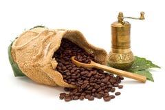 De koffiebonen morsten uit de zak met houten lepel en koffiemolen op groene bladeren Royalty-vrije Stock Afbeelding