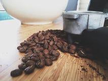 De koffiebonen op een lijst sluiten omhoog met een portiersfilter Stock Afbeelding