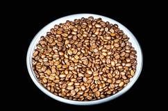 De koffiebonen op een ronde plateren dicht omhoog Ge?soleerde op zwarte achtergrond royalty-vrije stock foto