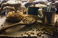 De Koffiebonen van de nadrukvlek en koffiekop op een houten lijst Stock Afbeeldingen