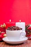 De koffiebonen van Kerstmis in een kop over rood Stock Afbeeldingen