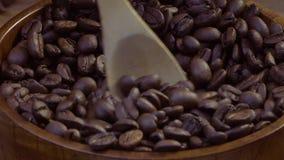 De koffiebonen worden gemengd met een houten lepel en in een houten lepel verzameld stock footage