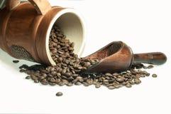 De koffiebonen worden gemorst van een mok op een witte oppervlakte stock foto