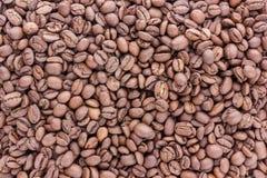 De koffiebonen zijn overal verspreid de oppervlakte royalty-vrije stock afbeeldingen