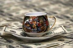 De koffiekop & geld van het porselein stock foto's
