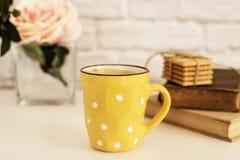 De koffiekop, de cappuccino, latte, de oude boeken, koekjes en namen op witte lijst toe Gray Brick Wall Het concept van de vrije  royalty-vrije stock fotografie