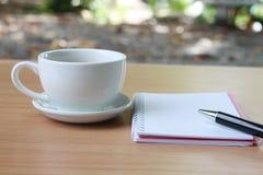 De koffiekop en de notitieboekjepen worden geplaatst op een bruine houten lijst a stock foto's