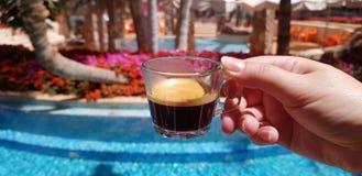De koffiekop maakte van transparant glas in vrouwelijke hand tegen blauwe openluchtpool stock afbeeldingen