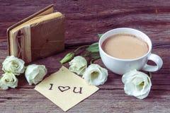 De koffiekop met lisianthus van de de lentebloem en nota's I houden van u Stock Fotografie