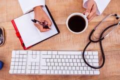 De koffiekop van de artsenholding en het schrijven op agenda Royalty-vrije Stock Afbeeldingen