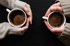 De Koffiekop van de handholding op donkere houten achtergrond Royalty-vrije Stock Afbeeldingen