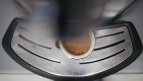 De koffiemachine maakt koffie in een witte kop De koffie giet uit de kop stock video