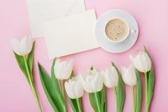 De koffiemok, document de kaart en de bloemen van de de lentetulp voor goedemorgen op roze lijst hierboven in vlakte leggen stijl Stock Foto