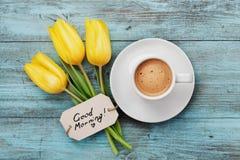 De koffiemok met gele tulp bloeit hierboven en neemt nota van goedemorgen op blauwe rustieke lijst van Royalty-vrije Stock Foto's