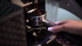 De koffiemolen maalt koffiebonen in een filterhouder stock videobeelden