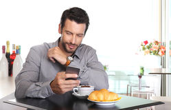 De koffiepauze, knappe mens gebruikt de slimme telefoon bij de bar met c royalty-vrije stock fotografie