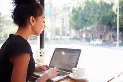 De Koffiewinkel van onderneemsterusing laptop in Royalty-vrije Stock Foto