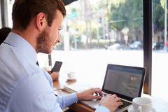 De Koffiewinkel van zakenmanusing laptop in Stock Foto