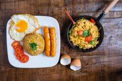 De kok American braadde rijst in een pan, met gebraden eieren en worsten wordt gediend die royalty-vrije stock foto's