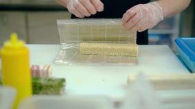 De kok bereidt een Japans broodje met rijst en sesamzaden voor stock videobeelden
