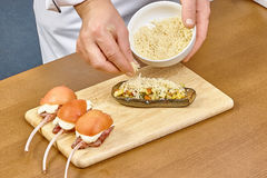 De kok bestrooit met kaas gevulde aubergine Royalty-vrije Stock Afbeeldingen