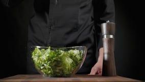 De kok bestrooit zout en kruiden aan groene salat op de zwarte achtergrond stock videobeelden