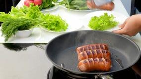 De kok beweegt gebraden worsten van een pan aan een plaat stock videobeelden