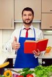 De kok bij keuken het tonen beduimelt omhoog Stock Fotografie