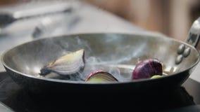De kok braadde uiplakken in een pan met forceps, in het kader van de hand stock videobeelden