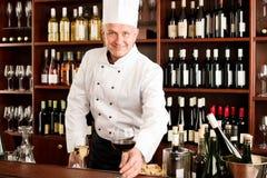 De kok die van de chef-kok dient het restaurant van het wijnglas glimlacht Stock Afbeeldingen
