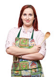 De kok die van de dame schort dragen, die een houten lepel houden Stock Foto's
