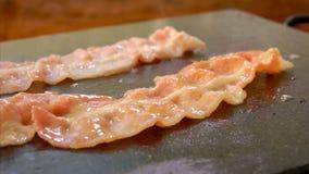 De kok draait bacon met metaaltang op de grill stock videobeelden