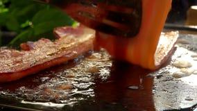 De kok draait bacon met metaaltang stock video