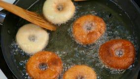 De kok draait donuts in olie stock video