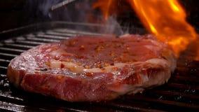 De kok drukt het lapje vlees op de grillrooster stock videobeelden