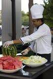De kok in een wit GLB snijdt een grote watermeloen royalty-vrije stock afbeelding