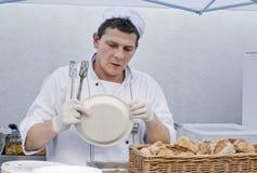 De kok in een witte kleding wil vers voedsel aan een plastic plaat opleggen Stock Afbeelding