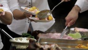 De kok en de kelners dienen geroosterd vlees bij de partij stock footage