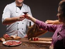 De kok geeft aan smaak rode wijn aan het meisje Een glas rode wijn en gehakte Mediterrane traditionele jamon Royalty-vrije Stock Foto