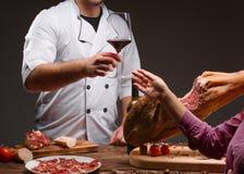 De kok geeft het proeven van de rode wijn aan het meisje Een glas rode wijn en gehakte Mediterrane jamon Royalty-vrije Stock Afbeeldingen