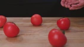 De kok giet een handvol tomaten op een scherpe raad stock videobeelden