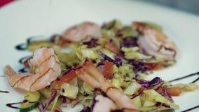 De kok giet een salade met garnalensaus stock videobeelden