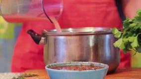 De kok giet sap van een karaf in een pan stock videobeelden