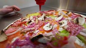 De kok giet de saus op de pizza stock footage