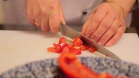 De kok hakte rode en gele groene paprikaclose-up stock footage