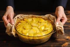 De kok houdt aardappelbraadpan met zijn handen royalty-vrije stock afbeeldingen
